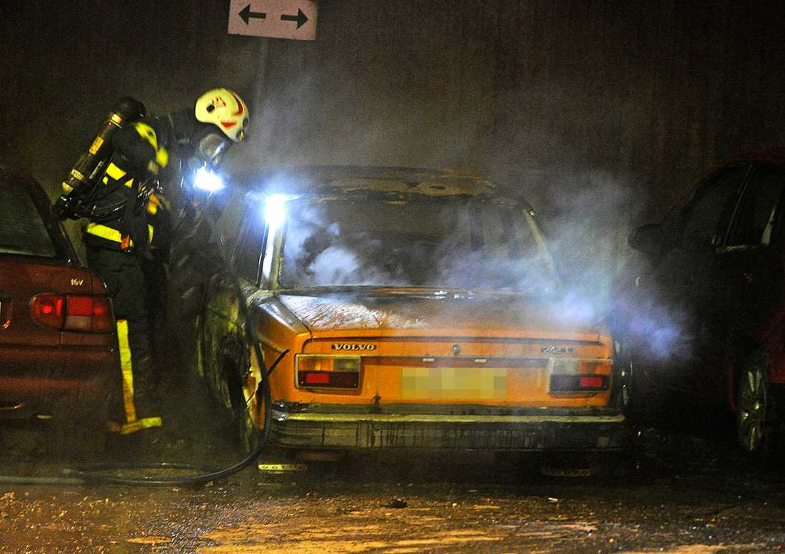 En brandman släcker en brinnande bil.