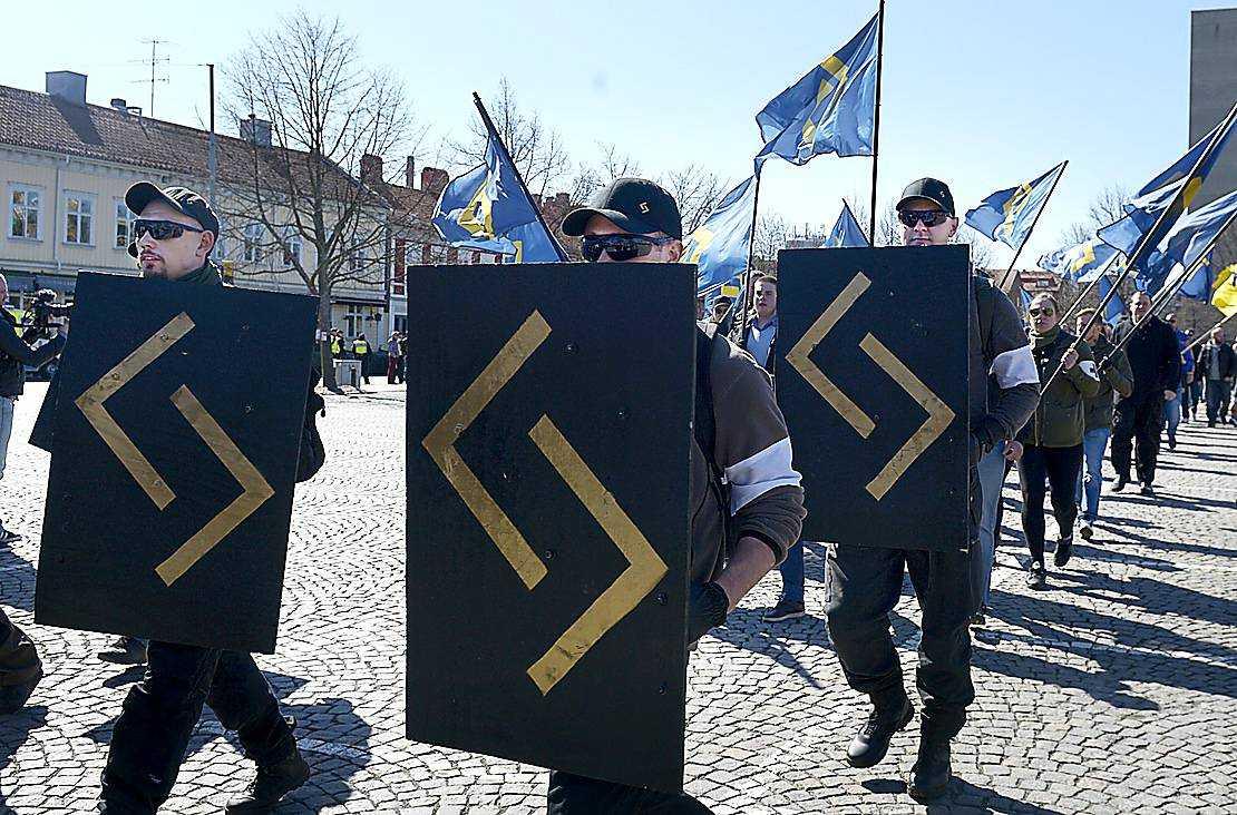 Medlemmar ur Svenskarnas parti gömmer sig bakom sköldar.