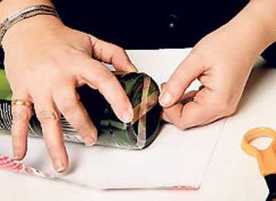 2. Tejpa flaskan med dubbelhäftande tejp på glaset, på två ställen så att det inte glider. Vik in den lösa kanten så att den är rak och fin. Tejpa och fäst den i kanten – även det som är löst ovanför flaskan, så att inte pappa kan kika in i överdelen.