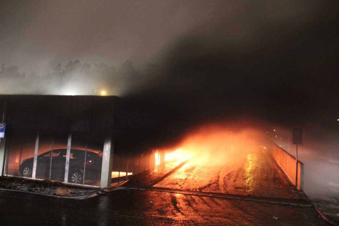 Bilar brinner i garaget.
