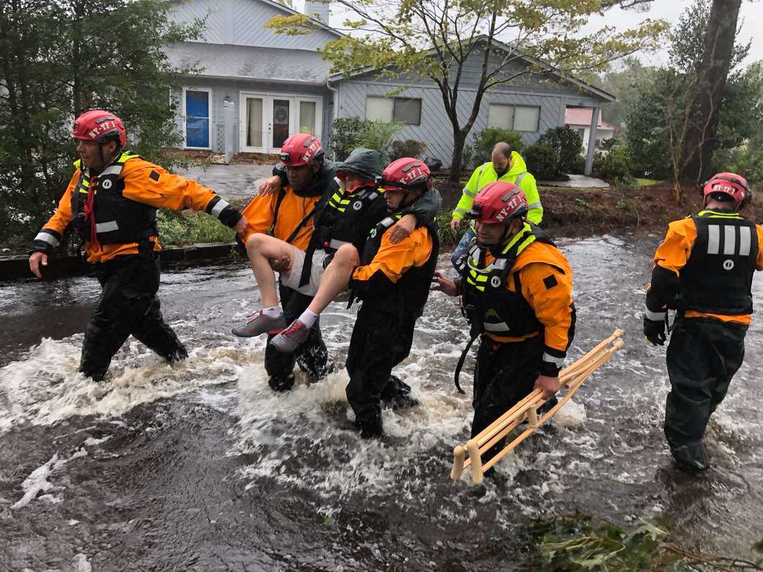 Räddningsarbetare från New York tar hand om en man på de översvämmade gatorna i River Bend, North Carolina.