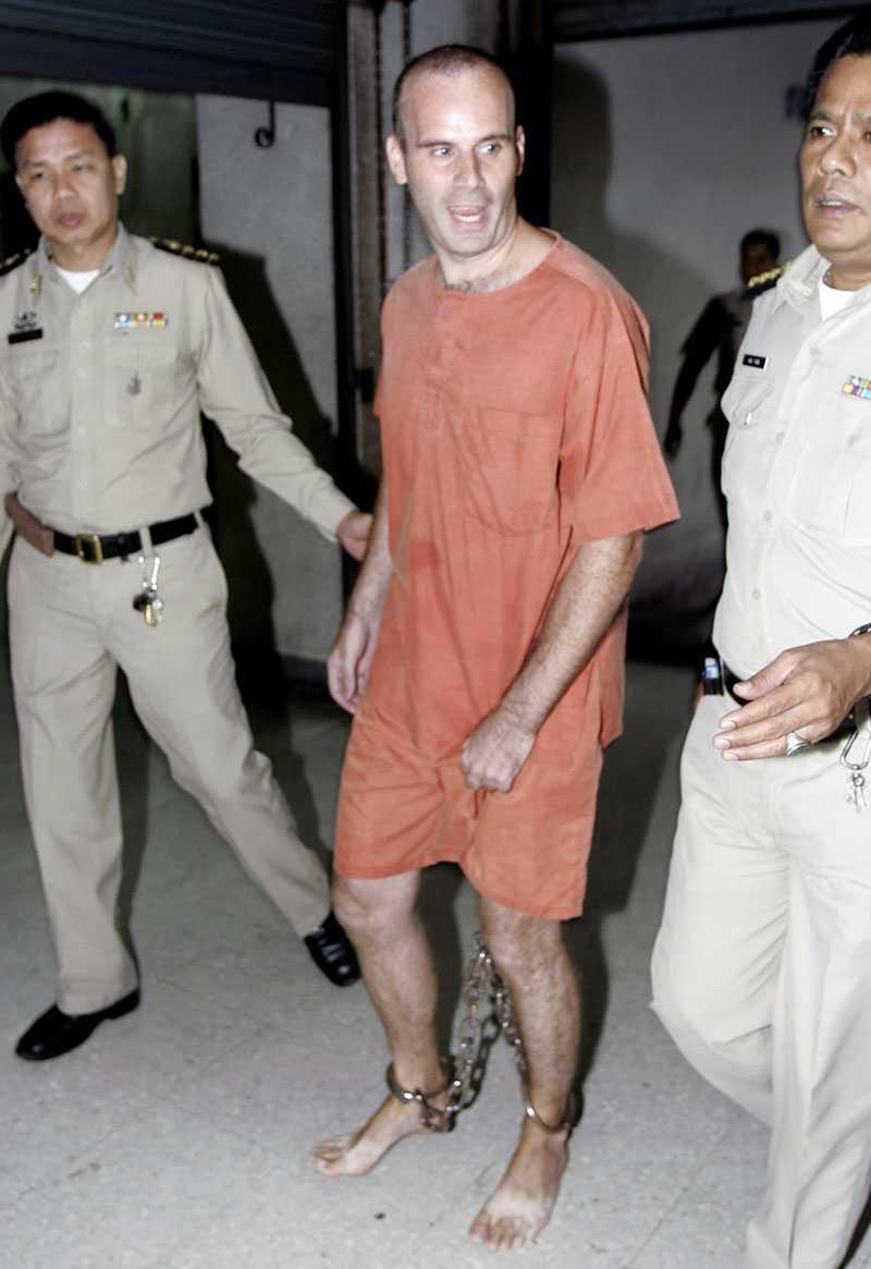 I bojor Christopher Paul Neil fördes in i rätten i orangea fångkläder och fotbojor.