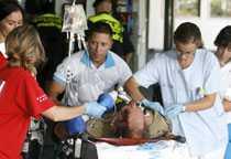 Sjukvårdspersonal tar hand om en av de överlevande vid flygplatsen Barajas utanför Madrid.