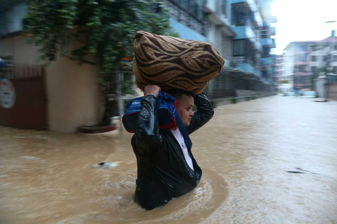 En nepalesisk man i fredags, då han vadade på en översvämmad gata i Katmandu med sina tillhörigheter.