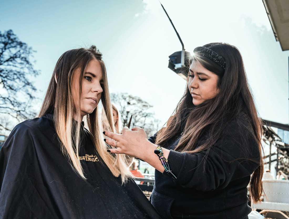 Frisören Fanny Ponce, här med kunden Evelina Salomonsson, klipper hår ute i det fria.