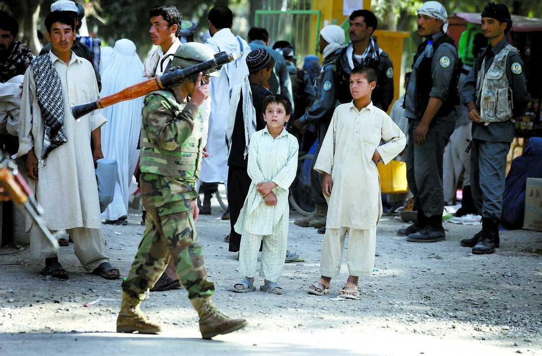 En soldat från ANA, Afghanistan National Army, patrullerar med raketgevär på axeln i centrala Balkh. Barnen tittar skräckslaget på.