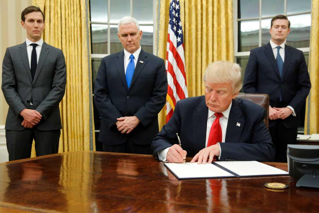 Jared Kushner, till vänster, tittar på när Trump skriver en exekutiv order. På bilden syns även vicepresident Pence.