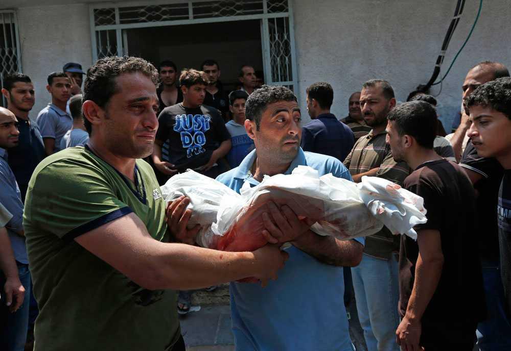 Palestinier i Gaza City bär en pojke som dog på söndagen till hans begravning.