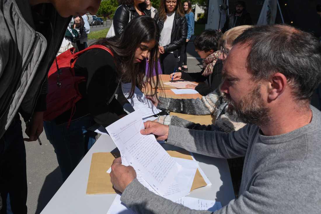 Studenten Luisa Mejias lämnar in en hemtenta till sin lärare, som fått sätta upp bord utanför en ockuperad byggnad för att kunna ta emot elevernas uppgifter.