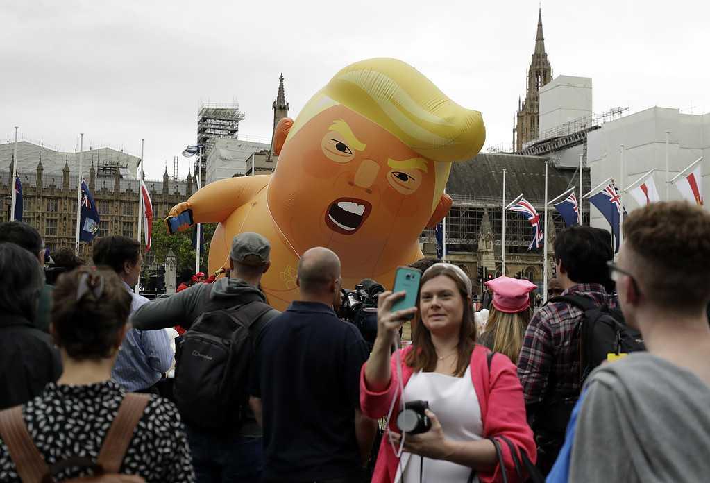 En stor balong föreställande president Trump som en arg baby tronar över protestanterna vid Parliament Square