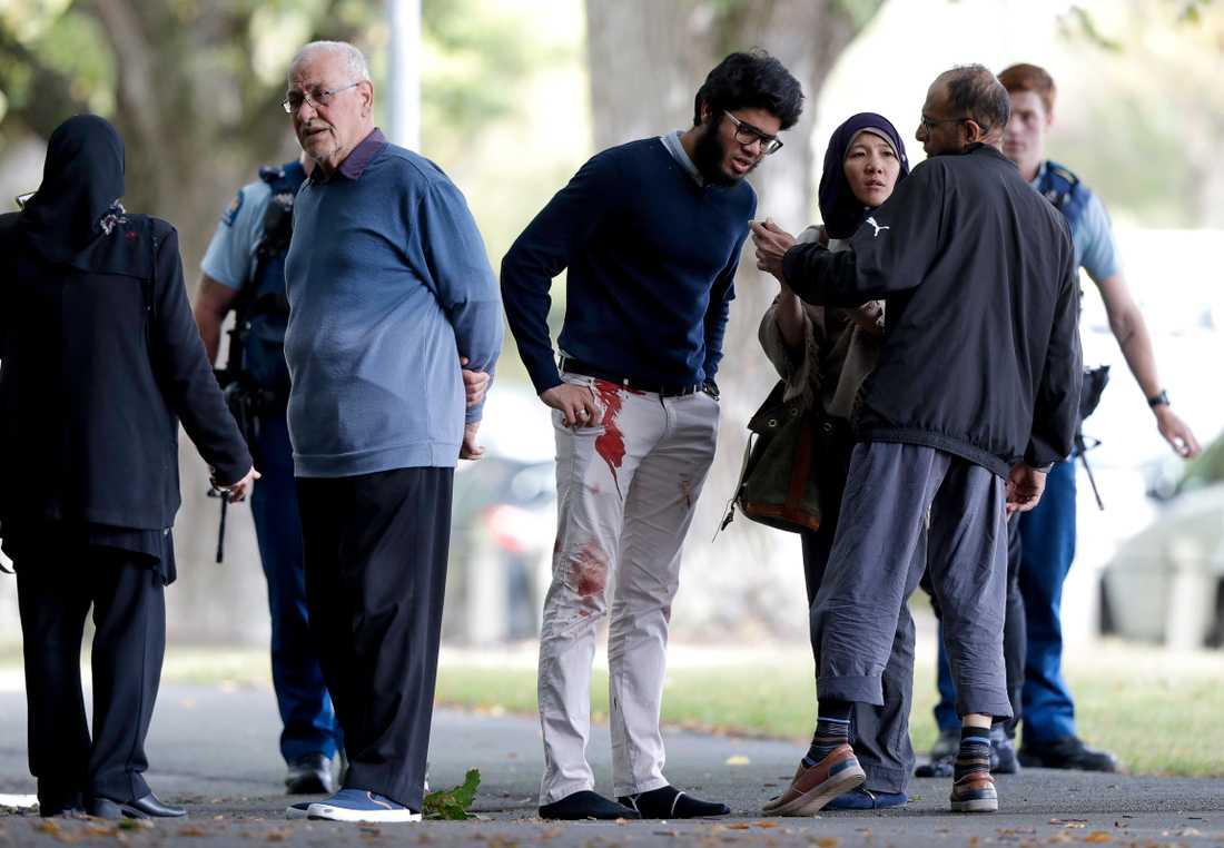 Människor står utanför en av de moskéer som attackerats i Christchurch på fredagen.
