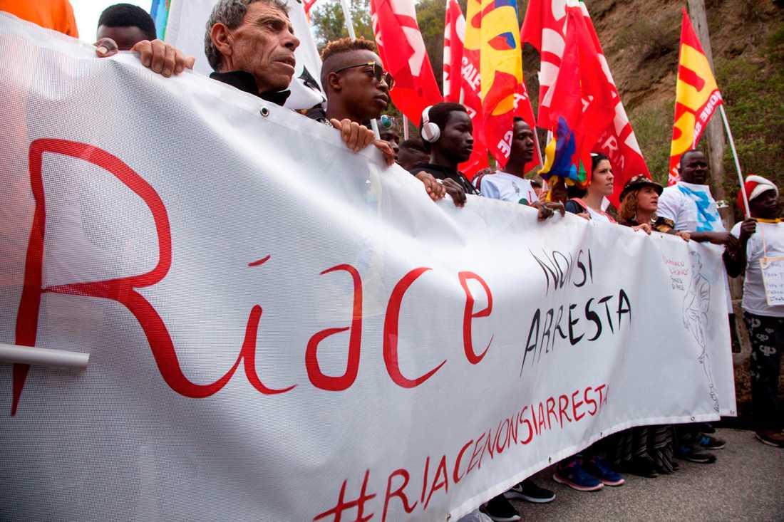 Protester i den lilla byn Riace efter att allt stöd till orten stoppats och borgmästaren arresterats. Riace gick mot strömmen och välkomnade tusentals migranter varje år – något som stack i ögonen på den invandrarfientliga regeringen.