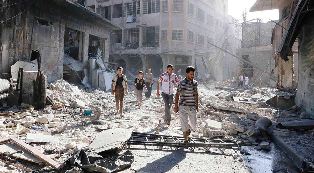 Personer undersöker en plats i staden Aleppo skadad av vad aktivister hävdar var en tunnbomb släppt av styrkor trogna Bashar al-Assad.
