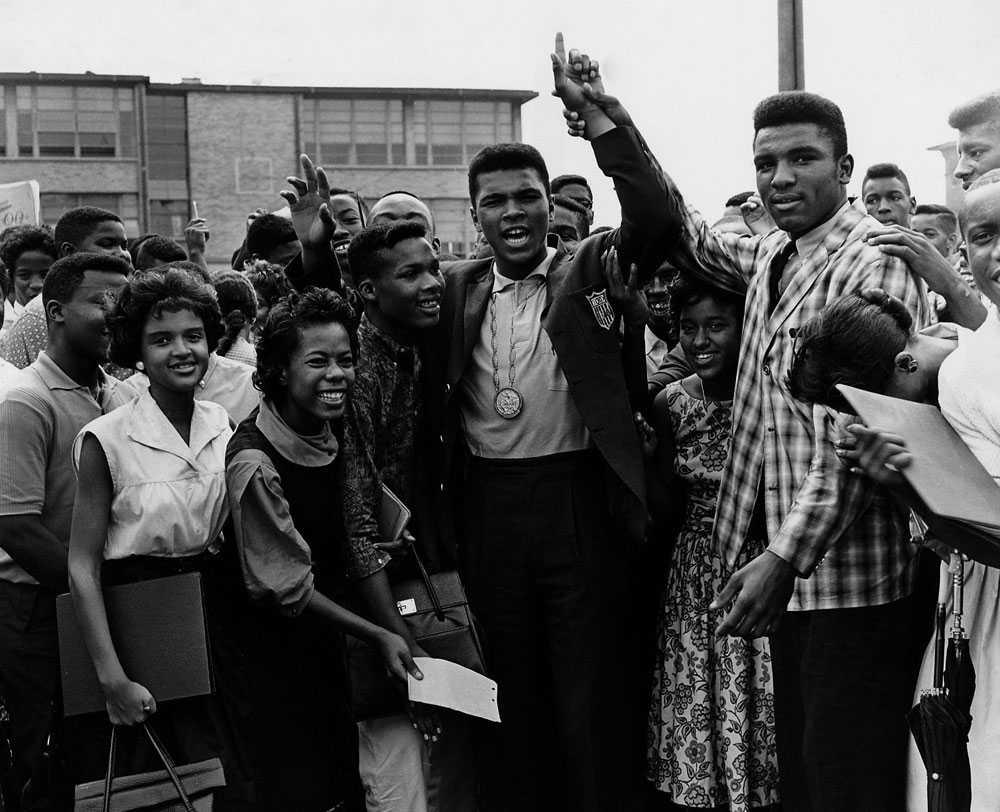 HEMMAHJÄLTEN Efter OS-segern 1960, här hyllas hemkomne Cassius Clay av studenter hemma i Lousiville, USA. OS-guldet hänger runt halsen på mästaren.