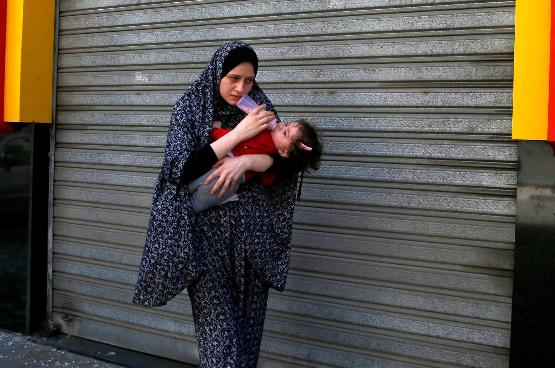 En kvinna boende i mediabyggnaden som bombade på lördagen flyr sitt hem innan bombningen. Israel uppmanade boende att evakuera innan bombningen.
