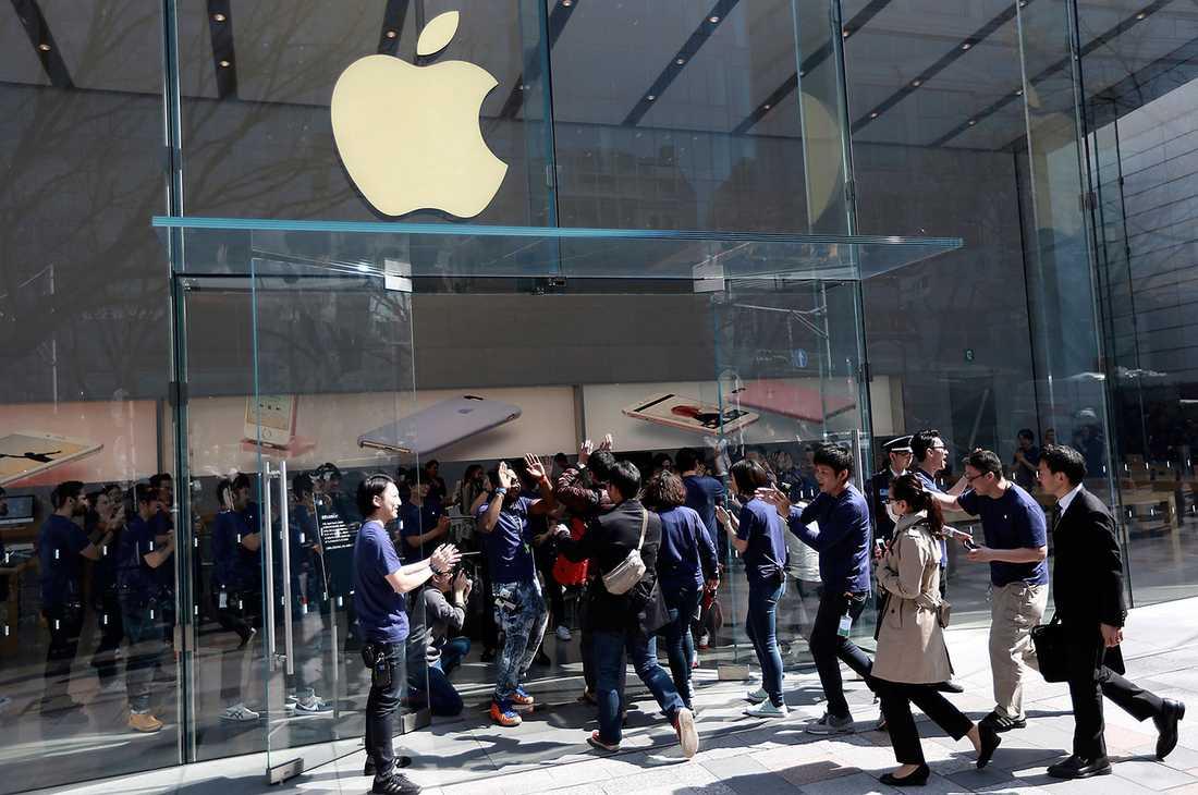 Säljarna i en Appleaffär i Japan tar emot de första kunderna som  köat för någon ny modell.