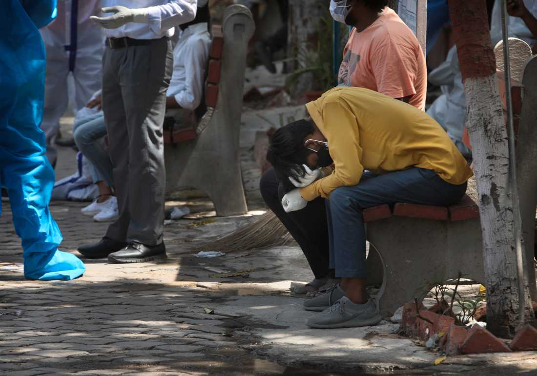 Sörjande anhöriga samlas för kremation av en person som nyligen avlidit i sviterna av covid-19 i Delhi, Indien.