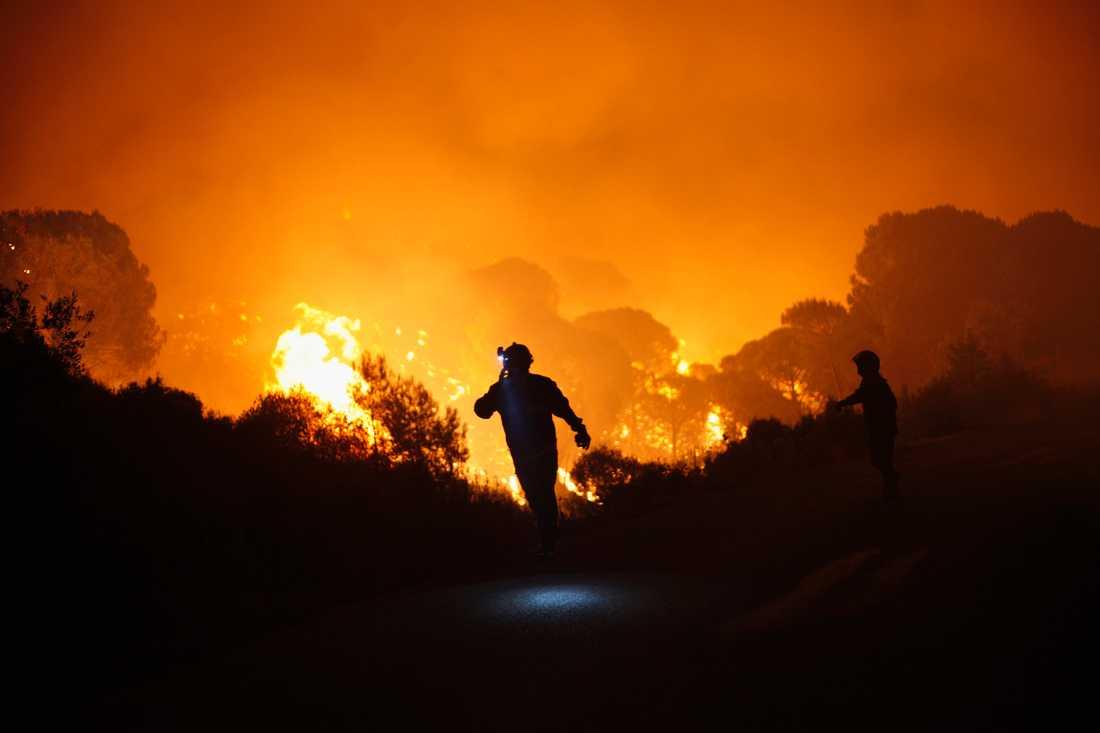 Brandmän försöker bekämpa elden, som nu sprider sig.