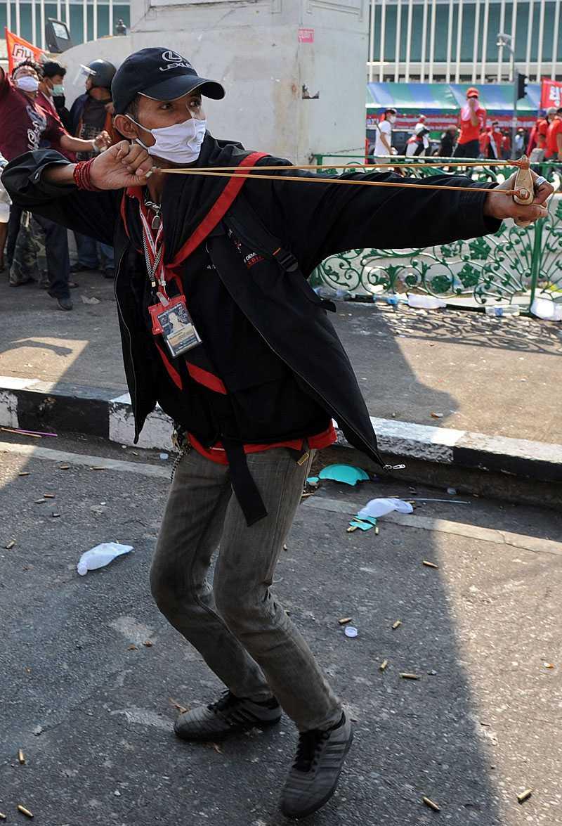 En demonstrant laddar sin slangbella med sten och siktar mot soldaterna.