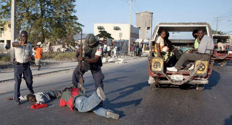 Polis arresterar en machetebeväpnad man. Trots ingripandet har polisen sedan länge förlorat kontrollen över huvudstaden.