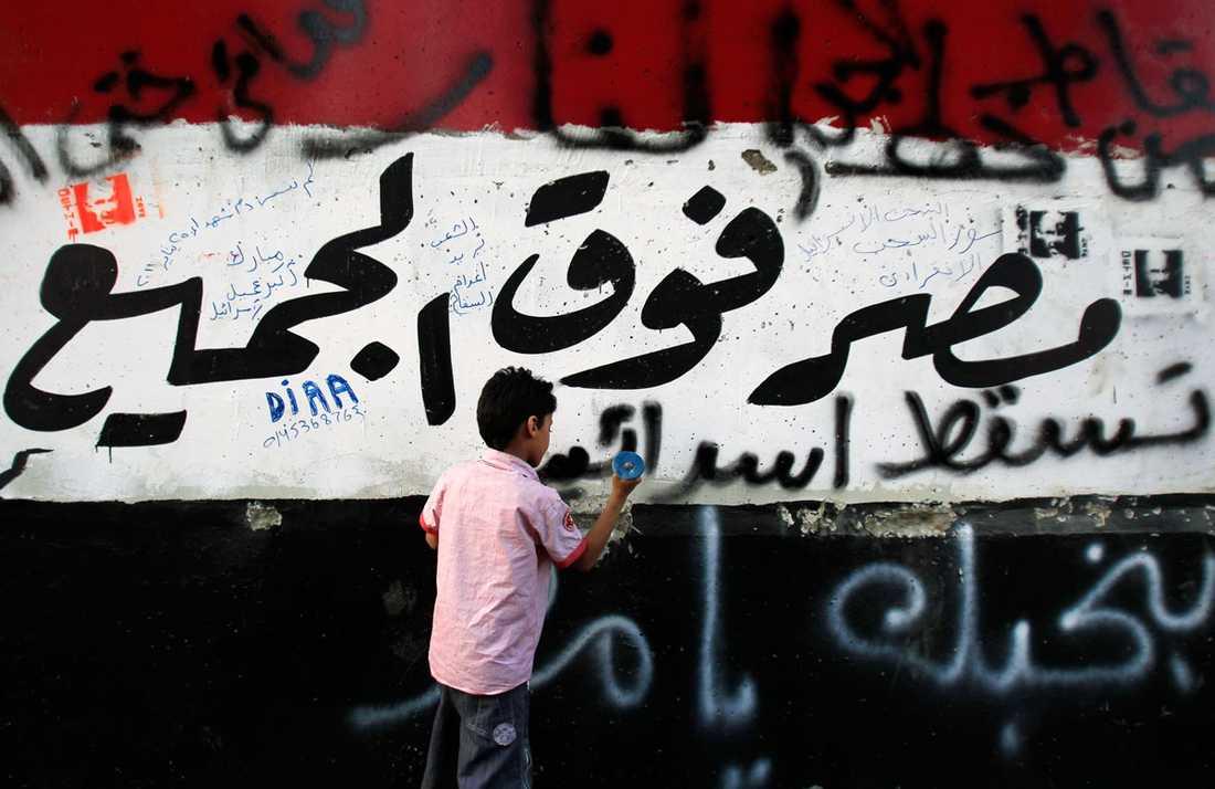 En ung demonstrant hackar på muren runt Israels ambassad i Kairo.