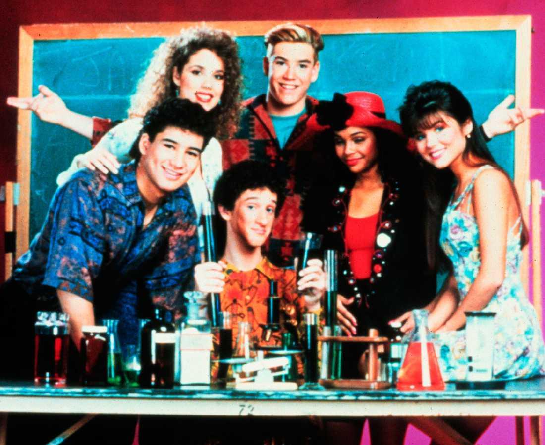 """Jessie, Zach, Lisa, Kelly, AC och Screech huserade i rutan under fyra år i början av 90-talet. Serien """"Pang i plugget"""" — eller """"Saved by the bell"""" som den hette på engelska — är än i dag en populärkulturell ikon. Ingen mindre än Justin Bieber har dykt upp med en Kelly Kapowski-tröja på röda mattan, och sjungit """"Call me Zack Morris / Cause I'm saving you by the bell"""" på sb.tv."""