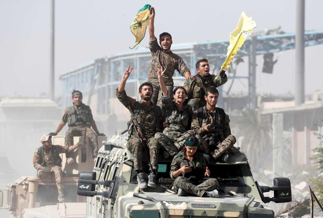 Syriska SDF-soldater firar segern i Raqqa.