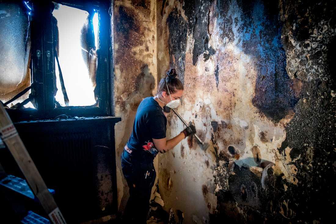 En polis går igenom resterna av moskén i Hässleholms