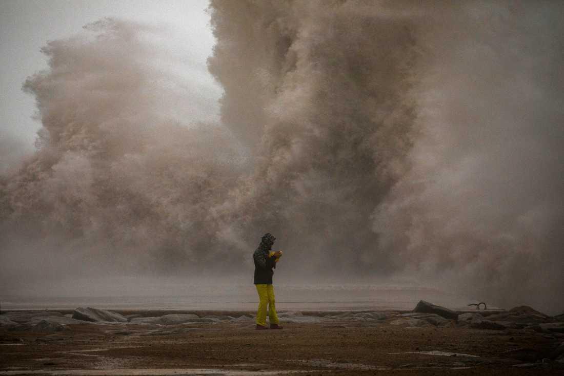 En kvinna i Barcelona fotograferar ett stormigt Medelhav. Bild tagen den 21 januari.