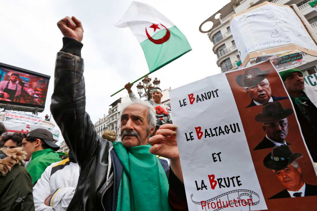 En man demonstrerar mot den styrande så kallade B-trion under en marsch i Algeriets huvudstad Alger i april. Han håller upp ett plakat med franska ord som börjar på B, som betyder ungefär banditer, odjur och maktens hantlangare.