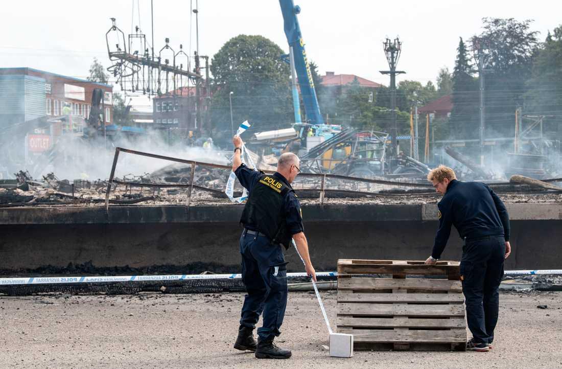 Polisens kriminaltekniker spärrar av medan de skadade kontaktledningarna och signalsystemkablarna demonteras och röjs undan strax norr om Hässleholm C efter en kraftig brand i augusti i en industribyggnad. Arkivbild.