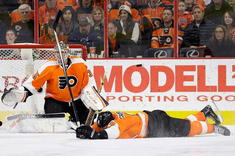 Nicklas Grossmann ligger utslagen på isen.