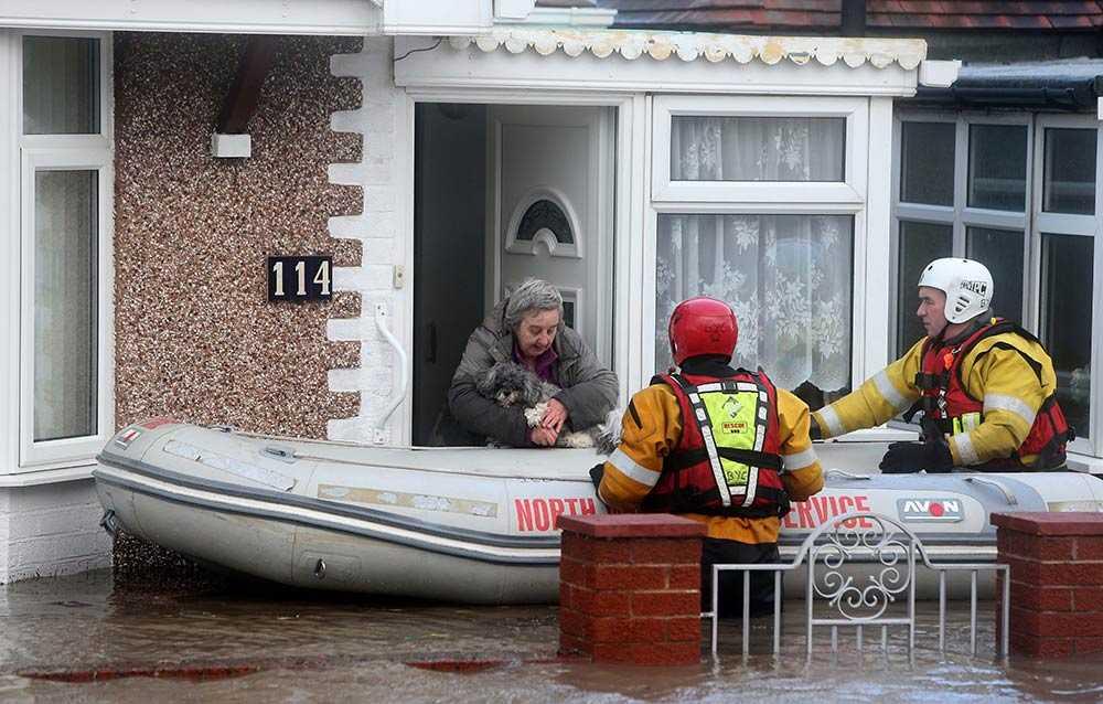 En kvinna och hennes hund räddas ur sitt hus i Rhyl, Wales. Staden har drabbats av kraftiga översvämningar till följd av ovädret.