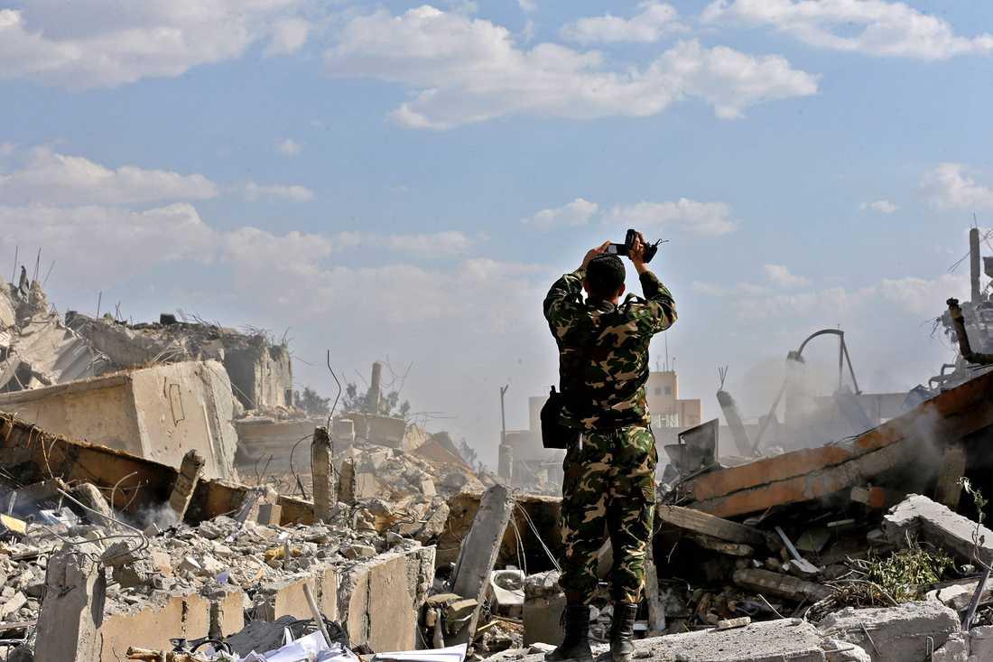 En syrisk soldat dokumenterar skadorna vid Scientific Studies and Research Centre (SSRC) vid Barzeh distriketet norr om Damaskus. Bilderna tagna vid en presstur som organiserats av Syriska informationsministeriet.