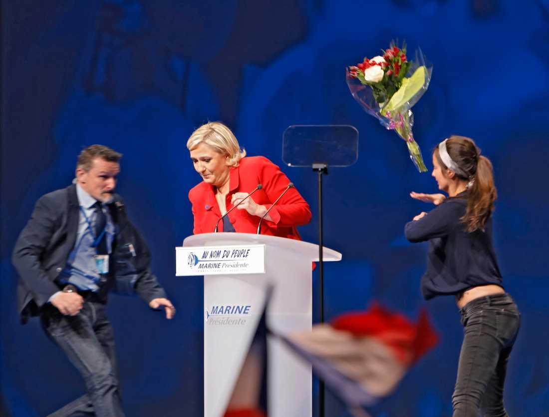 """Marine Le Pen överfölls av en """"Femen kvinna"""" som kastade blommor och försökte blotta sig."""