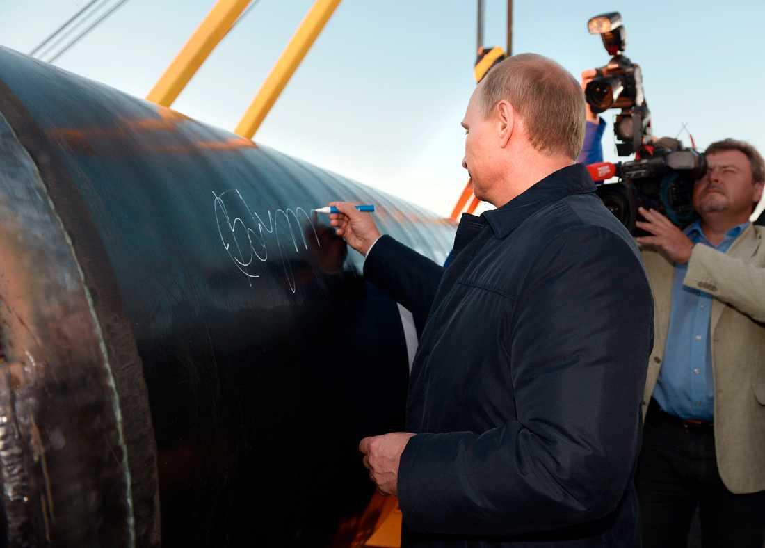 Vladimir Putin sätter sin autograf på pipelinen som ska föra gas från Ryssland till Kina.