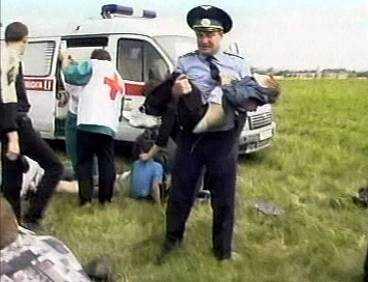 En militär försöker hjälpa en skadad pojke. Minst 78 dog och 138 skadades i den värsta olyckan någonsin på en flyguppvisning.