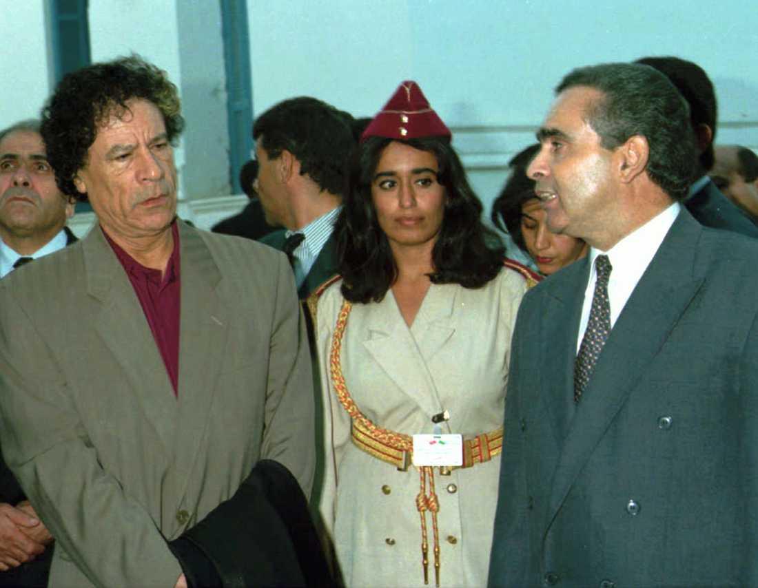Gaddafi pratar med en okänd tunisisk man 1996. Gaddafi har bara kvinnor i sin livvakt och en av dem syns i mitten.