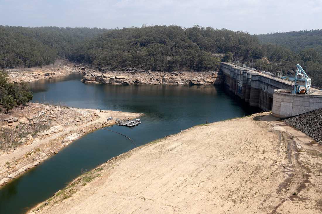 En flytande barriär har placerats i Warragamba-dammen för att skydda mot aska, som kan spolas med när regnet till slut faller över de branddrabbade områdena. Vattennivån i dammen är låg till följd av torka.