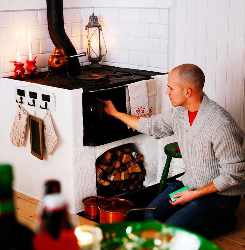 Eld i spisen är förstås ett måste i juletid. Tomas ser till att det brinner som det ska, och doften av värme fyller huset.