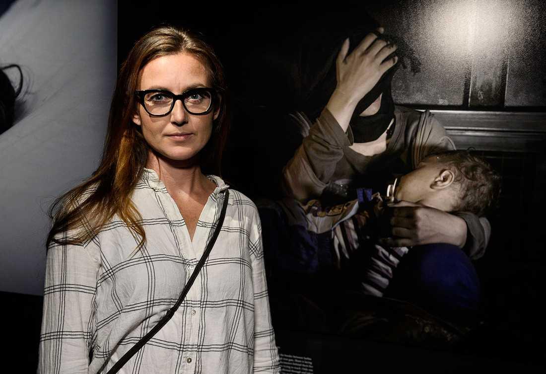 Journalisten Sanna Lundell framför sin favoritbild på utställningen: den av ettårige Sham och hans mamma vid järngrinden på gränsen mellan Serbien och Ungern.