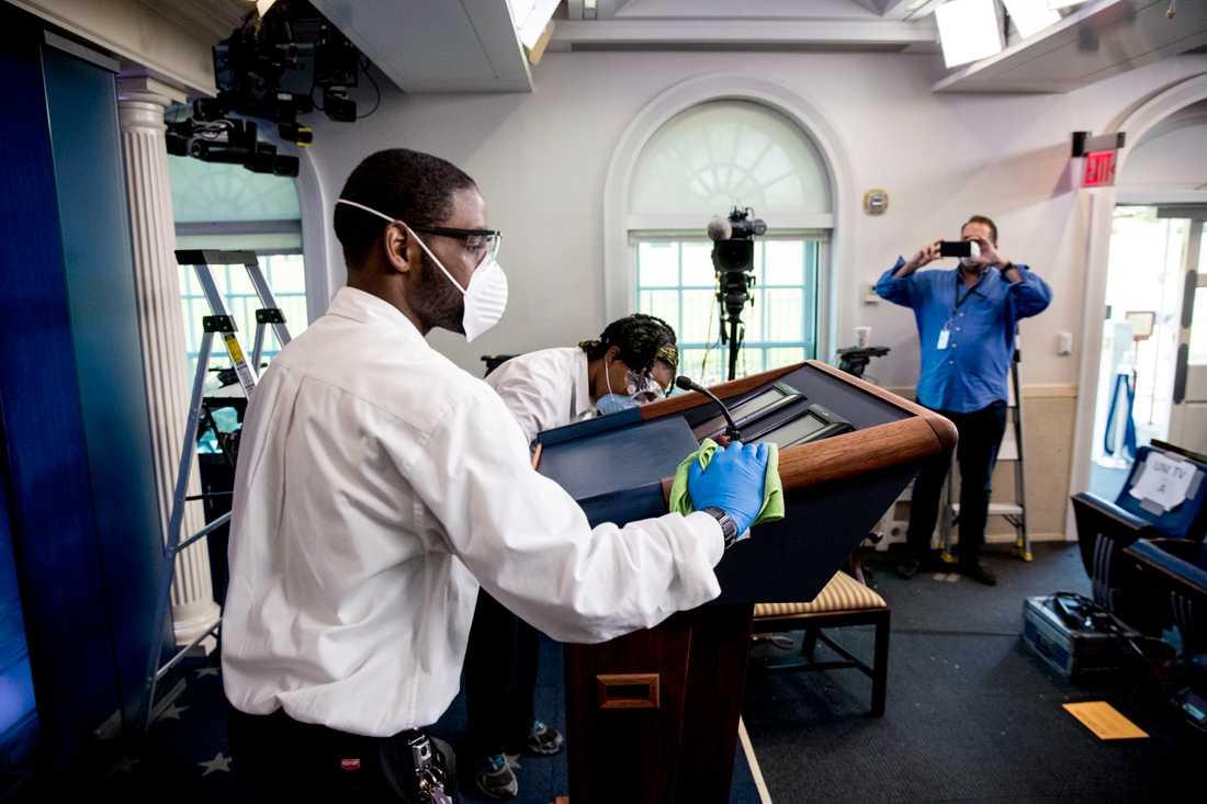 En Vita huset-anställd rengör president Trumps podium före pressträffen.