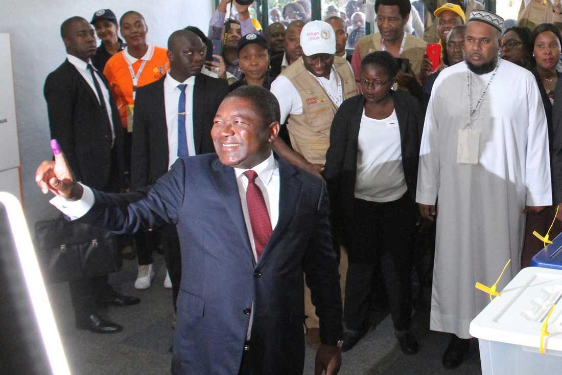 Moçambiques president Filipe Nyusi visar upp ett bläckfärgat finger för att visa att han röstat. Nyusi väntas bli omvald, men oppositionen väntas röna provinsiella framgångar.