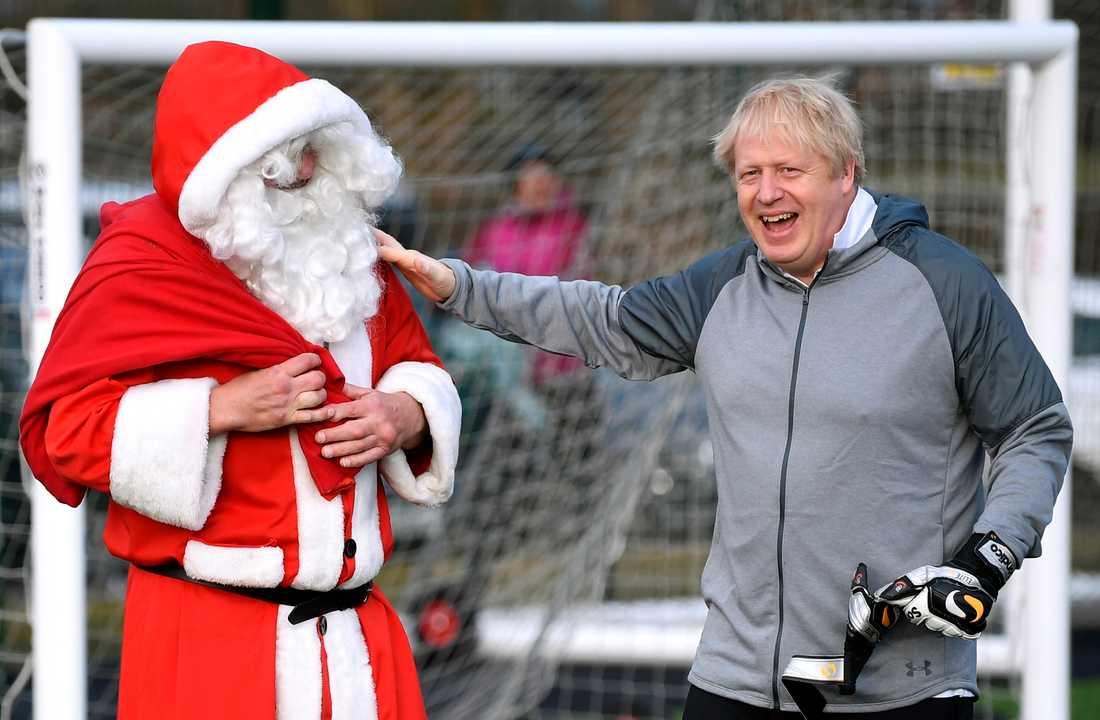 Storbritanniens premiärminister Boris Johnson hälsar på jultomten innan en fotbollsmatch som han besökte under ett stopp på sin valturné i Cheadle Hulme i lördags.