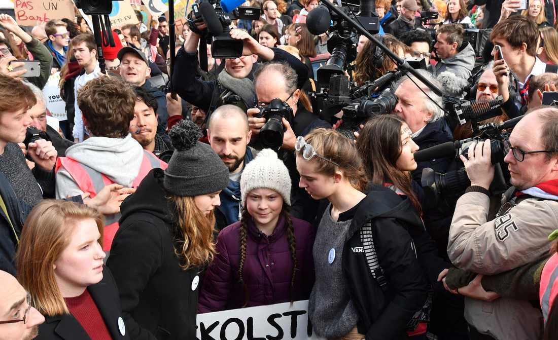 Svenska Greta Thunberg (mitten) omgiven av anhängare och journalister under en klimatdemonstration i Bryssel.