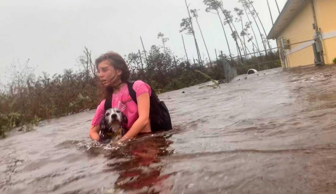 Freeportbon Julia Aylen och hennes hund evakuerar sitt översvämmade hem på ön Grand Bahama i norra Bahamas.