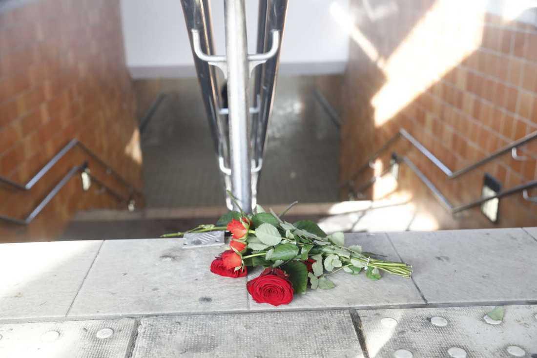 En bukett rosor ligger vid trappen till gångtunneln mellan perrongerna.