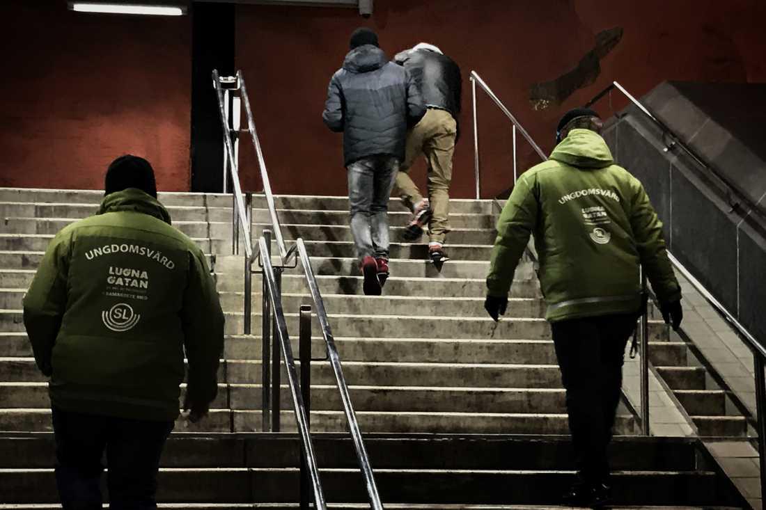 Två påverkade unga killar på Rinkebys tunnelbanestation lotsas ut av ungdomsvärdar från Lugna gatan.