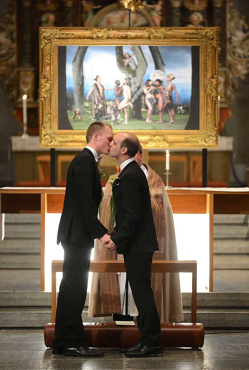 """nygifta  Det nygifta paret Magnus och Mattias i Skara domkyrka står framför Elisabeth Ohlson-Wallins altartavla """"Paradiset""""."""