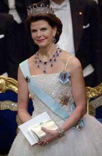 Drottning Silvia bar en vit sidenklänning med pärl- och glitterbroderier.